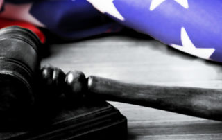 judge's mallet on desk with american flag