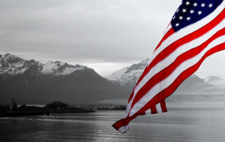 US flag over Alaska skyline and mountains