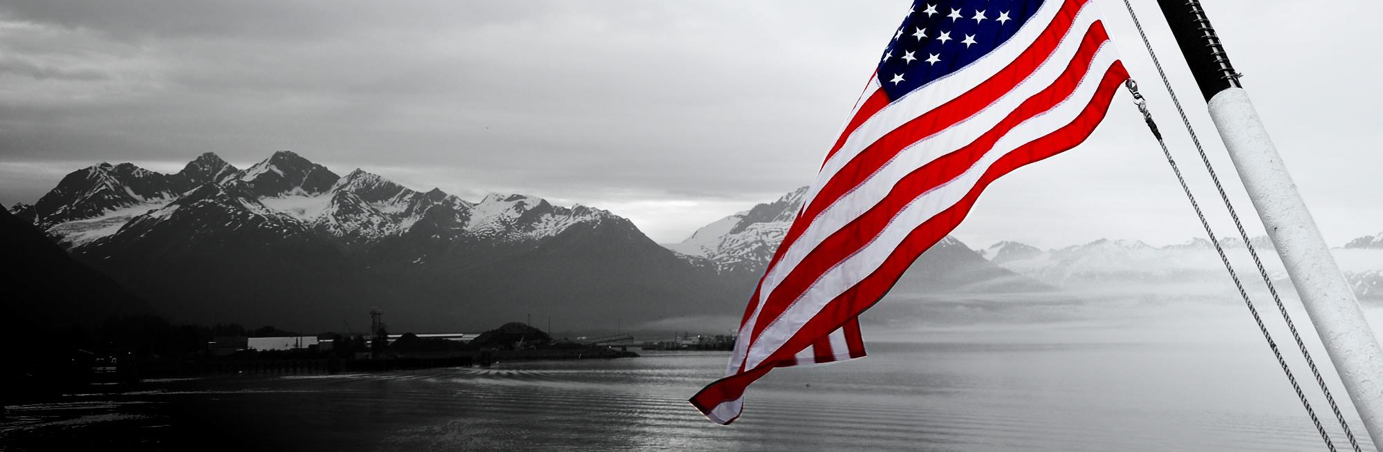 US flag over Alaska skyline and mountains